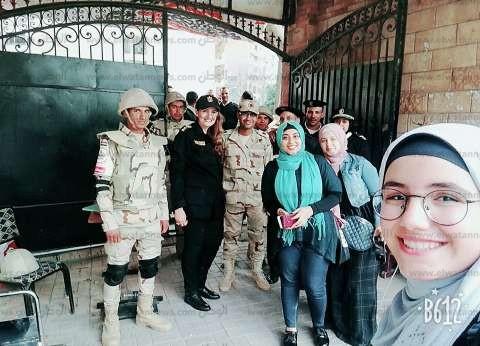 تحت الراية المنصورة.. ناخبون يلتقطون الصور مع أفراد الشرطة والجيش