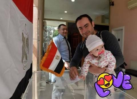 """رضيعة برفقة أبيها يمسكان بورقة الاقتراع.. و""""الجالية"""": أصغر مصرية تنتخب"""