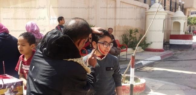 """""""رزق وفن ومشاركة"""".. """"أشرف"""" يرسم علم مصر على الوجه بجنيه في الإسكندرية"""