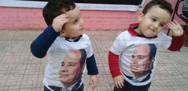 """توأم بـ""""تي شيرت السيسي"""" برفقة أبويهما بطابور الانتخابات: """"نفسنا نصوت"""""""