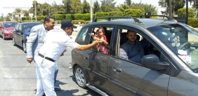 بالصور  أمن نفق الشهيد أحمد حمدي يوزع الورود على المواطنين