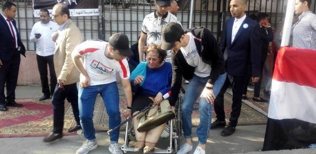 """شباب """"إعمل الصح"""" يحملون عجوزا للإدلاء بصوتها في تعديل الدستور بالنزهة"""