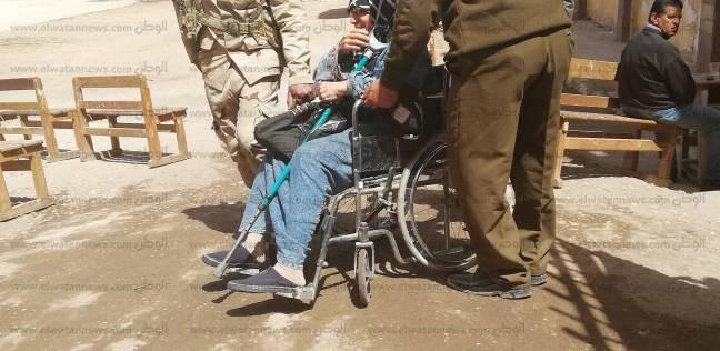 أفراد من الجيش والشرطة يساعدون مسنة للوصول للجنتها