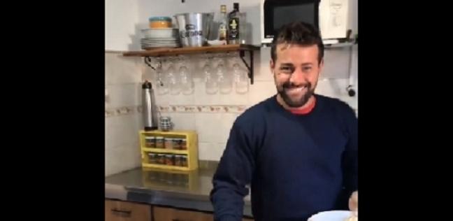 رجل يحمل في يده أطباق الطعام في مقطع من فيديو الأغنية الإسبانية Mi mujer me gobier