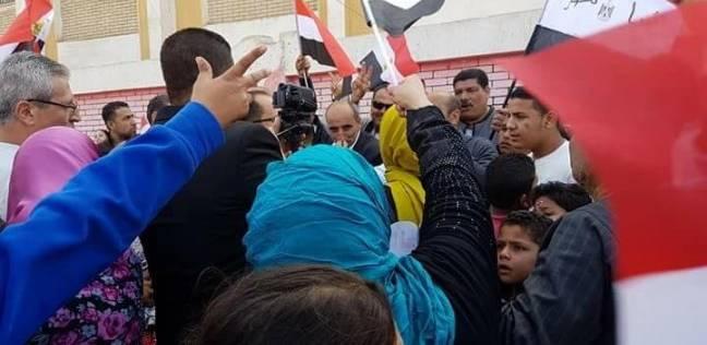 ناخبون يرفعون رايات وأعلام مصر أثناء إدلائهم بأصواتهم بلجان السنطة