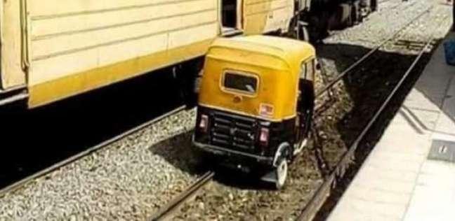 توك توك يسير بجانب قطار