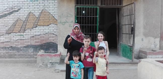 """سيدة تصطحب أبنائها الثلاثة في الانتخابات: """"فرح وجايين نشارك"""""""