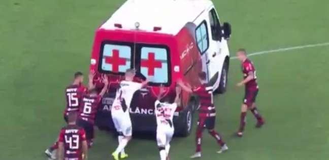 تعطل عربة إسعاف في ملعب كرة قدم واللاعبون يدفعونها
