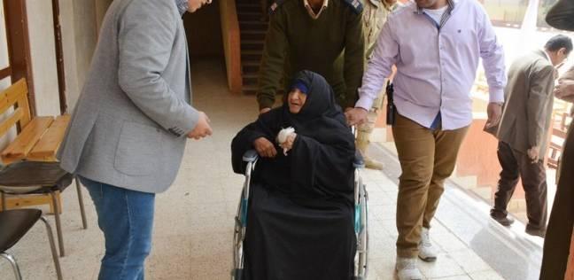 قاض يخرج من اللجنة بكشف الناخبين ليساعد مسنة في التصويت بسوهاج