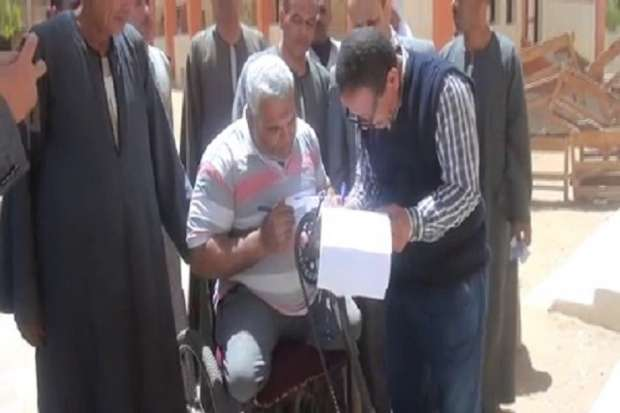 """رئيس لجنة يساعد """"متحدي إعاقة"""" على التصويت في الفيوم"""