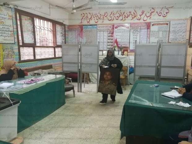 """شقيقة """"صائد التكفيريين"""" تحمل صورته خلال تصويتها ببني سويف"""