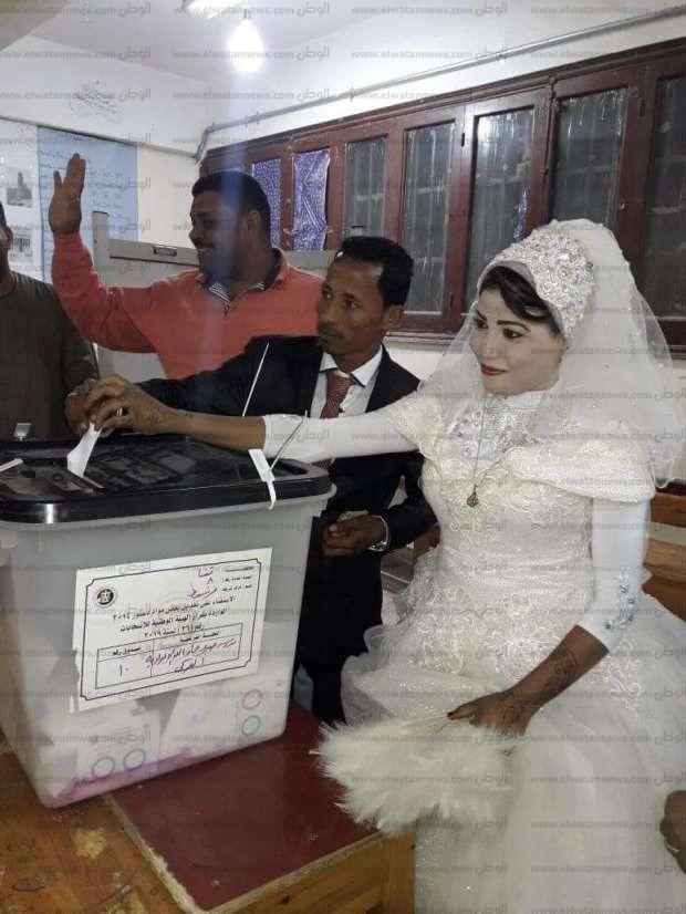 بالصور| عروسان يدليان بصوتيهما بملابس الزفاف داخل لجنة بقنا